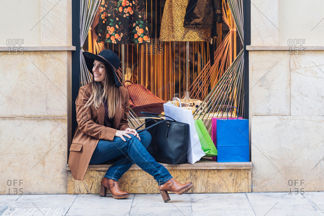 Stylish long haired female wearing a hat shopaholic in casual fashionable wear sitting with shopping bags on rocked fence of shop window while smiling and looking away at city street