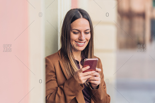 Satisfied charming lady in stylish casual clothing and heels leaning on wall of building talking on the mobile phone looking away at city street