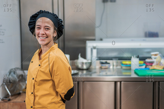Cheerful young female chef in yellow uniform and black hat looking at camera while  standing in restaurant kitchen