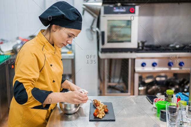 Side view of serious young female chef garnishing and finishing gourmet dish ready for serving while working at table in restaurant kitchen