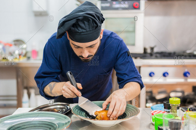 Focused professional male cook using spatula and putting food on plate while preparing for serving in restaurant kitchen