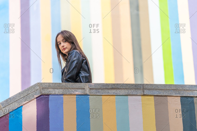 Side view of attractive pensive young woman in jackets standing on different level of striped colored stairs outdoors looking at camera