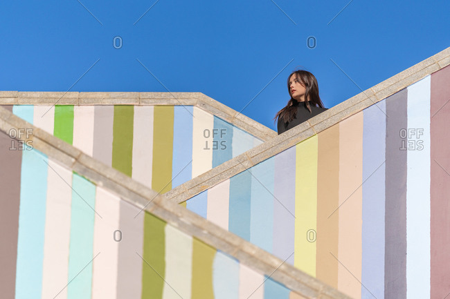 Side view of attractive pensive young woman in jackets standing on different level of striped colored stairs outdoors looking away