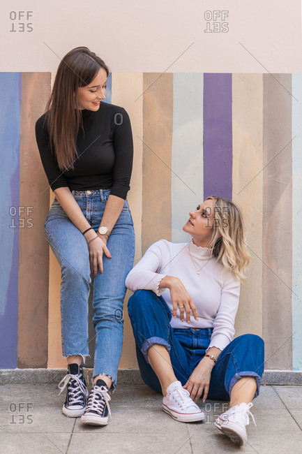 Smiling positive elegant women sitting while leaning on stripped colorful wall close to sidewalk on the street looking at each other