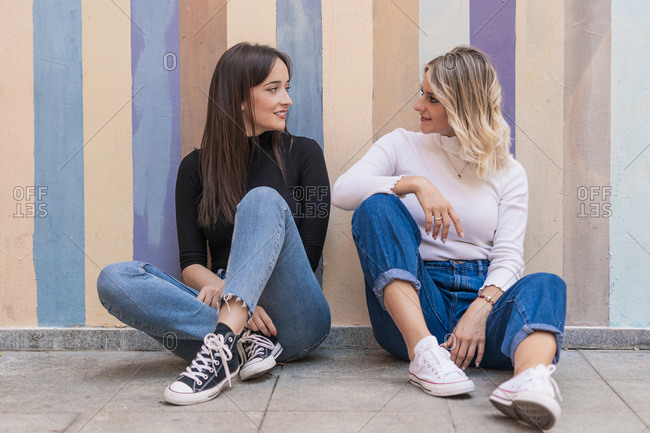 Smiling positive elegant women leaning on each other while sitting close on sidewalk near striped street wall looking at each other