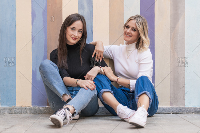 Smiling positive elegant women leaning on each other while sitting close on sidewalk near striped street wall looking at camera