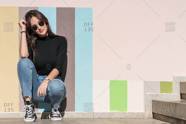 Positive gorgeous carefree woman in stylish outfit and sunglasses leaning on painted urban wall while sitting alone in sunny day
