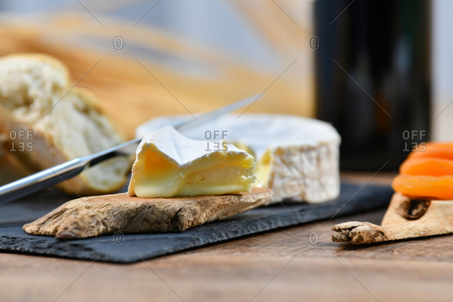 Delightful various types of white cheese and crispy fresh bread with pieces of wood on rustic table