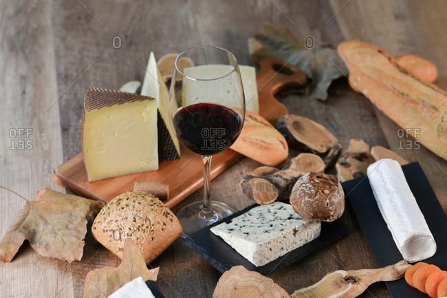 From above tasty homemade slices of white cheese and fresh crusty bread with bottle and glass of red wine on rustic wooden table