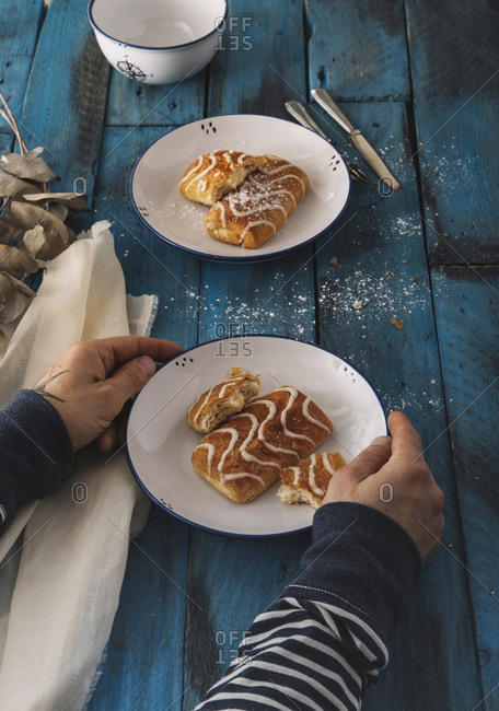 From above unrecognizable person taking piece of homemade delicious fresh sweet rolls laying on plates on blue wooden table