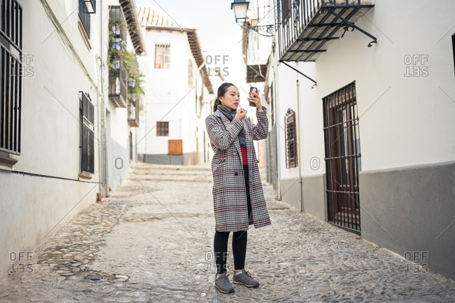 Young Asian female traveler in stylish casual coat refreshing makeup while looking in screen of mobile phone among tight street at Albaicin in Granada