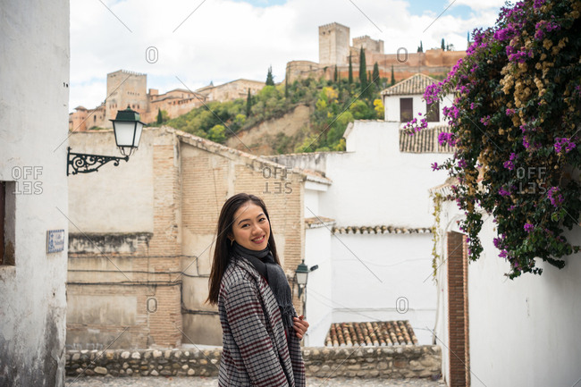 Side view of pleased Asian female tourist in stylish coat looking at camera with ancient rocked buildings and beautiful castle on background at Alcazar of Alhambra in Granada