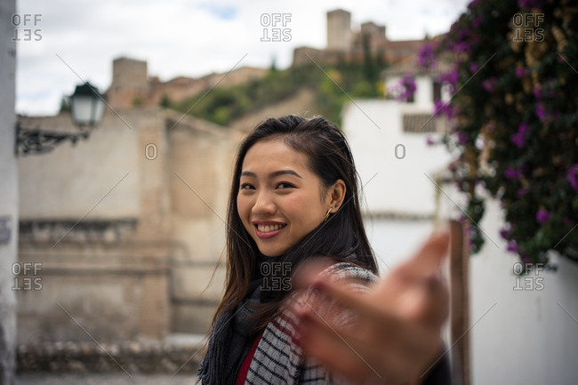 Asian female traveler in warm wear smiling among old buildings near big castle