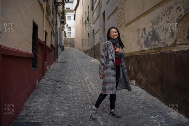 Joyful Asian resting female hiking on old rocked narrow street