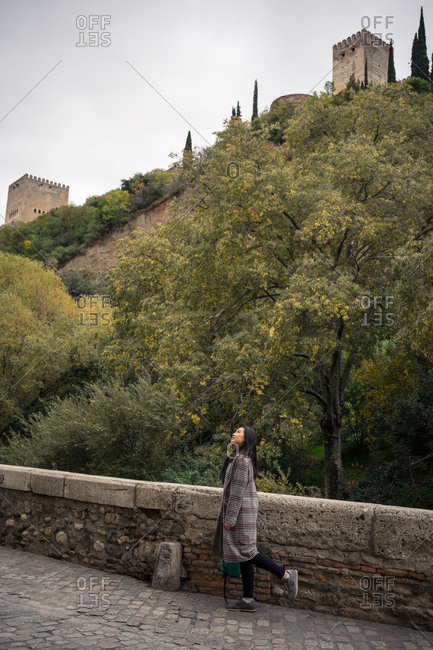 Side view of black haired female traveler in casual coat standing on aged cobblestone bridge with fence and green hill with ancient castle at Alcazaba of Alhambra in Granada