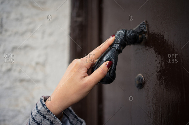 Curious female traveler in casual wear clattering in ancient door at city street