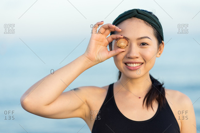 Cheerful smiling young Asian female in sport shirt looking at camera and covering eye with sea shell while standing on beach with blurred blue water and sky in background