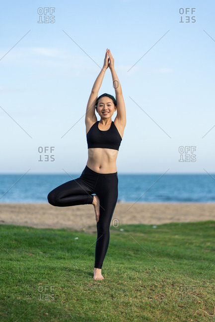 Young slim female in black top and leggings standing in tree pose on green grass while practicing yoga on beach