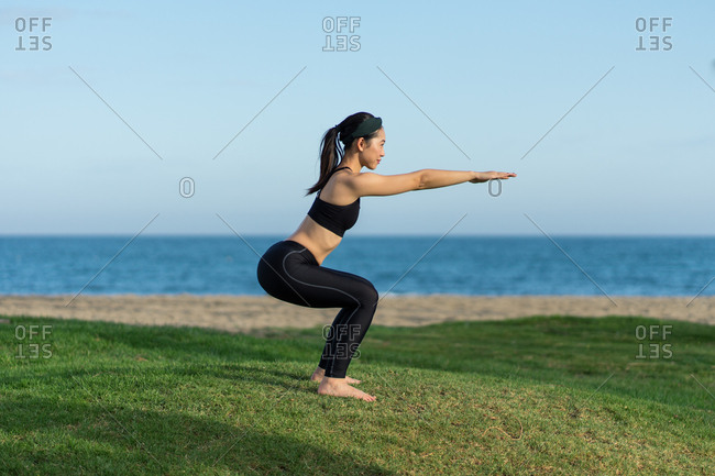 Young slim female in black top and leggings standing on green grass practicing yoga on beach