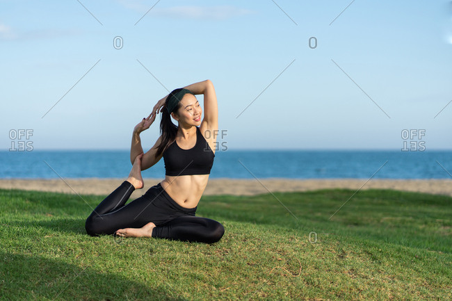 Young slim female in black top and leggings sitting on green grass practicing yoga on beach