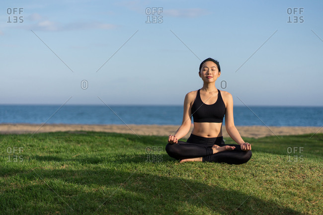 Young slim female in black top and leggings sitting on lotus position on green grass with closed eyes while meditating at the beach