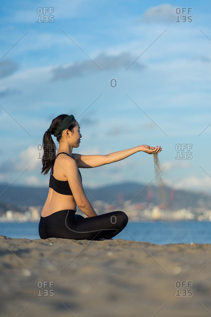 Side view of young fitness female in black sportswear sitting with crossed legs on beach and pouring sand through fingers while resting after workout