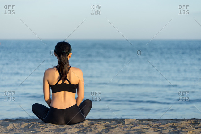 Back view of young fitness female in black sportswear sitting with crossed legs on beach resting after workout