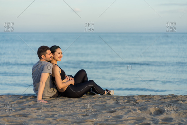 Side view of cheerful young multiracial couple in sportswear sitting on sandy beach while resting after training and enjoying time together