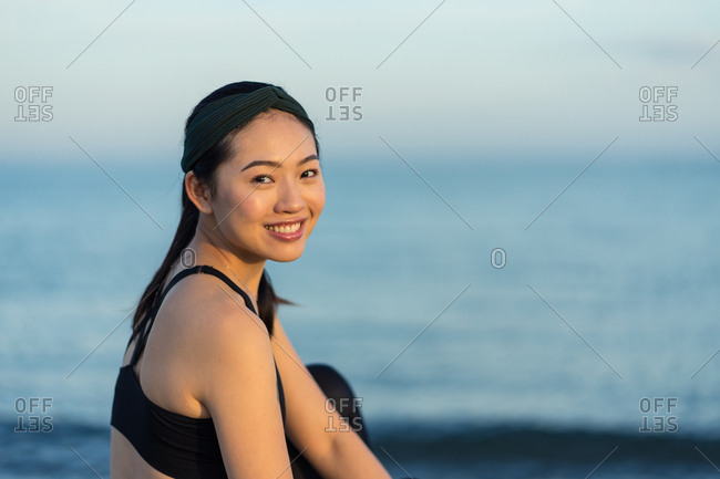 Side view of smiling young fitness female in black sportswear sitting with crossed legs on beach resting after workout looking at camera