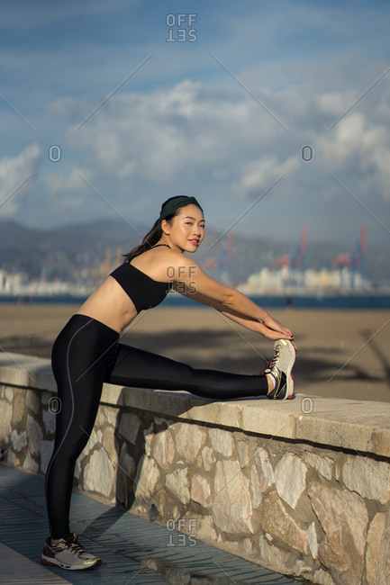 Side view of young Asian female in black top and leggings doing stretching exercise while standing next to stone fence at seaside
