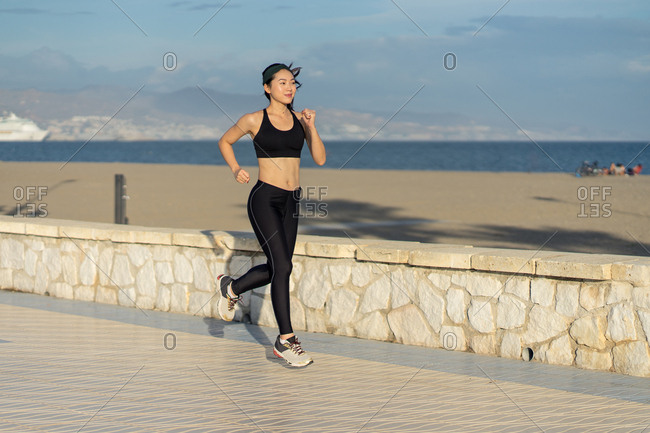 Motivated young female athlete in active black wear and sneakers jogging along rocky fence by the beach on empty seashore