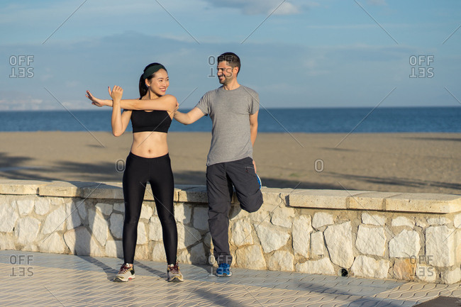 Pleased young sporty couple standing in one legs while holding to each other in sports clothing with blue seas and sky on blurred background