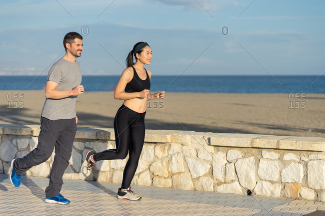 Healthy content couple in sports clothing smiling while jogging by the ocean side coast on blurred background