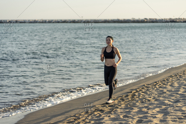 Motivated young female athlete in active black wear and sneakers jogging along sandy empty seashore