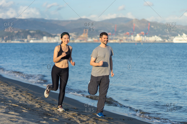 Healthy content couple in sports clothing smiling while jogging on sandy ocean side with city on opposite coast on blurred background