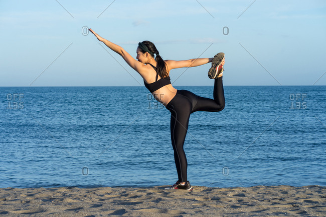 Strong young female athlete in black sports clothing standing on one leg while holding another leg with raised hand and looking at camera with com blue sea and sky on background
