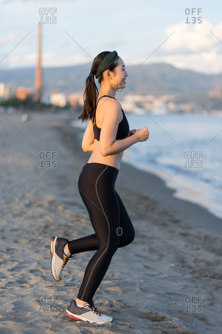 Side view of motivated young female athlete in active black wear and sneakers jogging along sandy empty seashore
