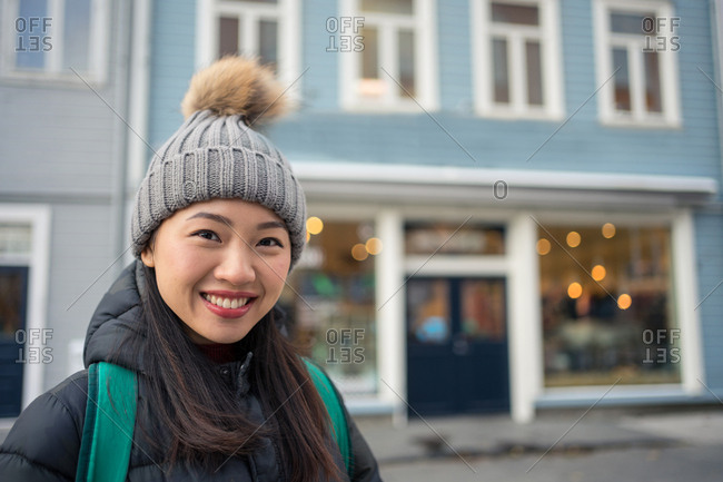 Gorgeous adult Asian female in warm clothes looking at camera and smiling against blurred exterior of blue modern building in downtown