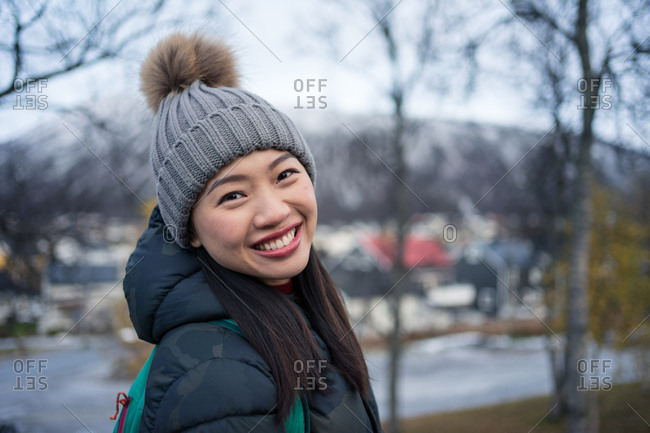 Attractive adult Asian woman in warm clothes with backpack smiling at camera while standing on street against blurred exterior of amazing triangle shaped church and snowy hills in Norway
