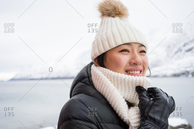 Happy female with amazing eyes in black jacket and white warm hat and scarf looking away and smiling against white blurred background in Norway