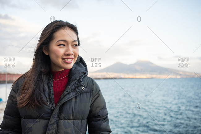 Satisfied resting female in warm clothing enjoying view of beautiful on seashore at Naples at Italy