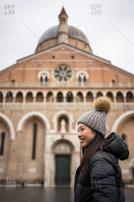 Side view of pleased Asian female traveler in warm clothing and hat smiling and looking away with old big Basilica of San Antonio on blurred background at Padova at Italy