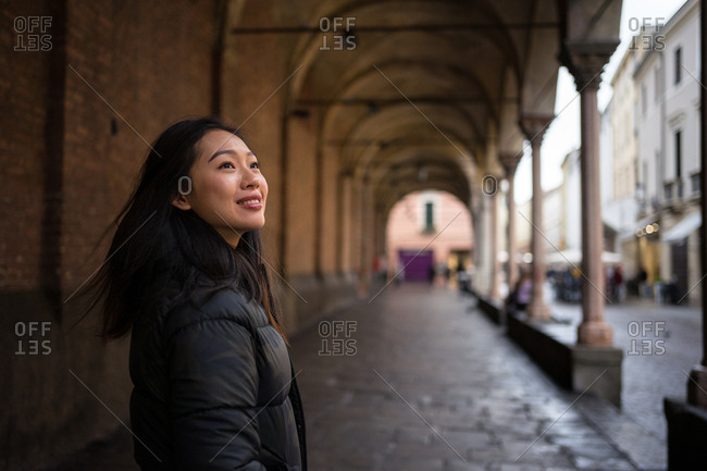 Content Asian resting female smiling wile exploring ancient streets with rocked roads and buildings with columns and looking away at Papua at Italy
