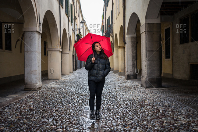 Young Asian female traveler in warm clothing sightseeing using red umbrella with old buildings on blurred background at Padova at Italy