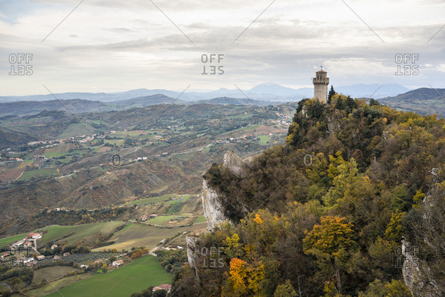 Ancient castle on peak overgrown with green trees raising high into gray sky in San Marino, Italy