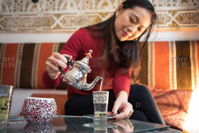 Happy ethnic female pouring fresh Arabic tea in cup while sitting on comfortable couch in small ornamental room