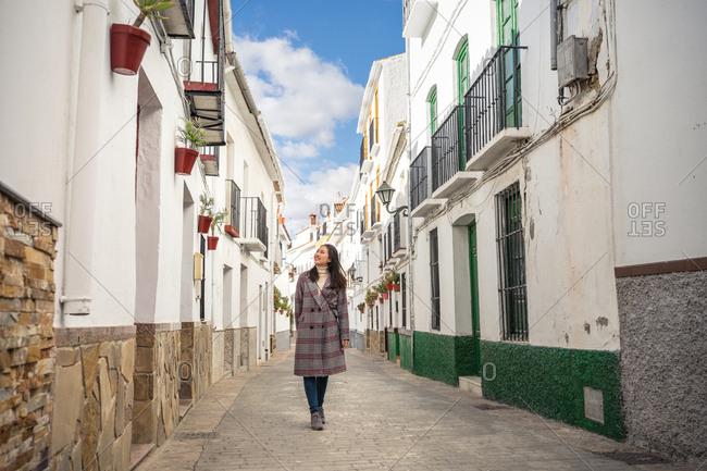 Happy female strolling on empty narrow street
