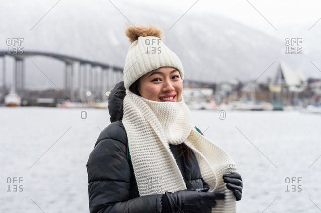 Content Asian female traveler in warm clothing standing and looking at camera with modern city on blurred background at Tromso in Norway