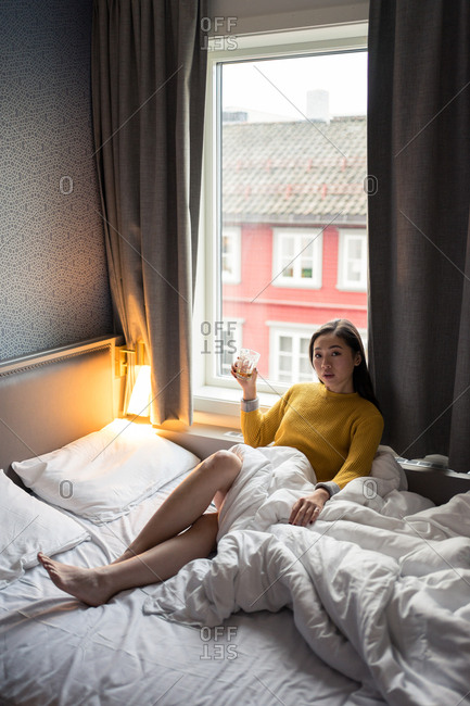Asian woman in yellow sweater sitting on bed while drinking tea leaning in a window on lazy morning at Tromso in Norway