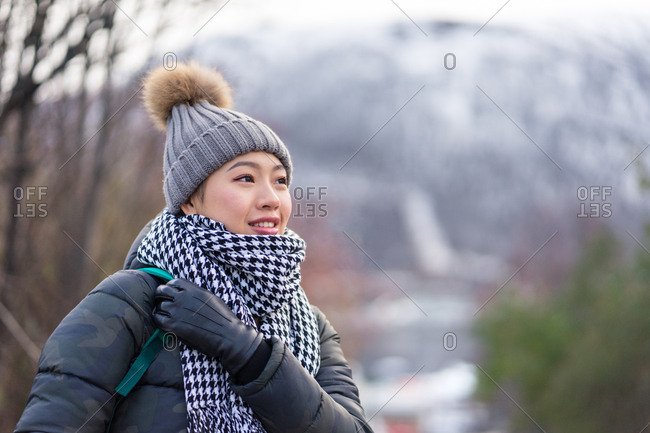 Happy Asian female traveler in warm clothing smiling and looking away with mountain on blurred background at Tromso in Norway